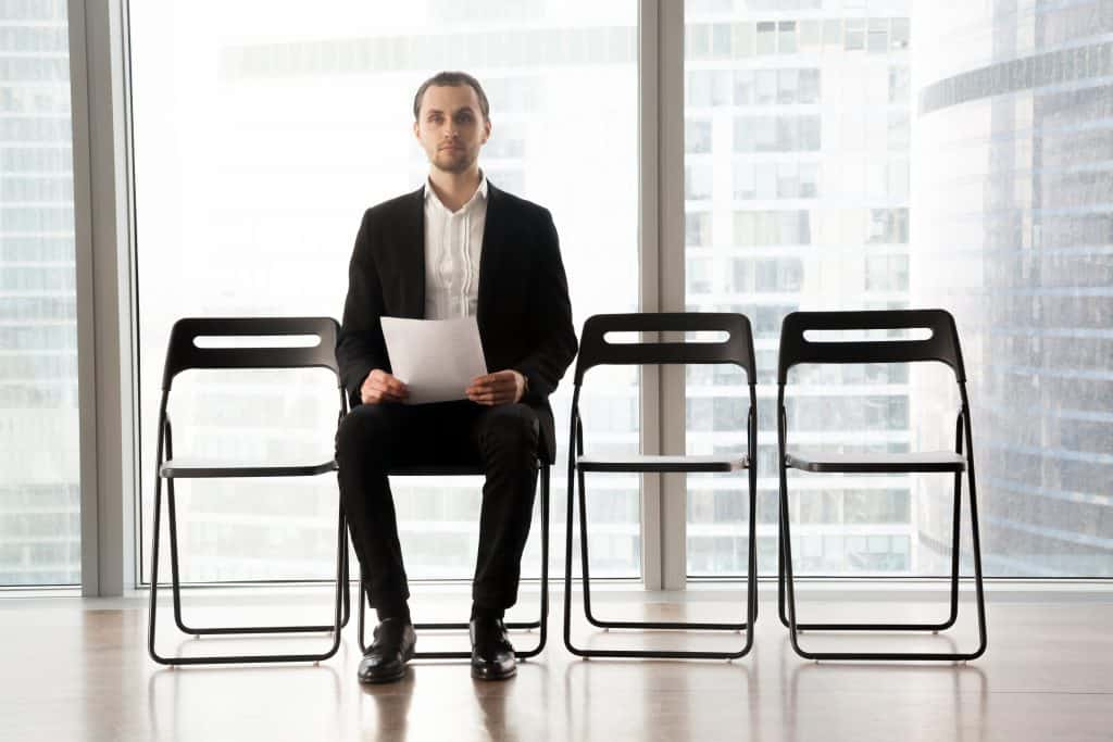 Young male candidate on post sitting on chair in office with resume in hands. Job applicant worries before talk with employer, trying to stay calm while waiting his turn on interview in waiting room